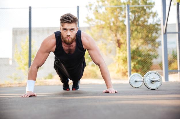 Ritratto di un giovane atleta barbuto concentrato che fa esercizio di plancia all'aperto