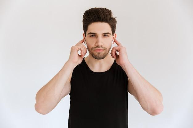 Ritratto di un giovane sportivo concentrato isolato sopra musica d'ascolto della parete bianca con gli auricolari.