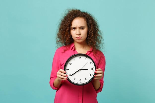 Ritratto di ragazza africana interessata in abiti casual rosa che tiene orologio rotondo isolato su sfondo blu turchese parete in studio. persone sincere emozioni, concetto di stile di vita. mock up copia spazio.