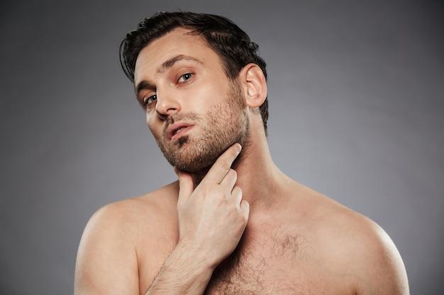 Ritratto di un uomo senza camicia interessato che esamina il suo fronte