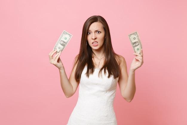 Ritratto di donna sconvolta preoccupata in abito bianco con in mano banconote da un dollaro