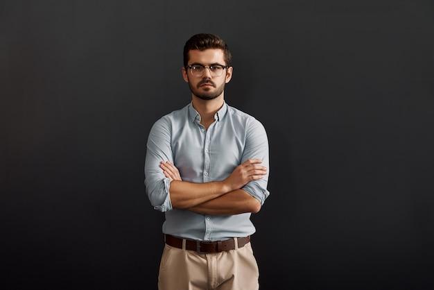 Ritratto di fiducia serio giovane uomo barbuto che guarda l'obbiettivo e tiene le braccia incrociate mentre