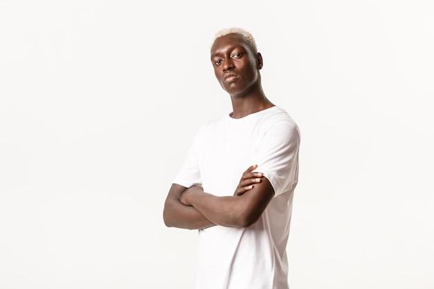 Ritratto di fiducioso assertivo ragazzo afro-americano con capelli biondi, petto di braccia incrociate e aspetto impertinente