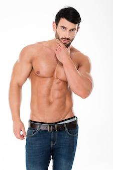 Ritratto di un uomo atletico fiducioso con il torso nudo in piedi isolato su un muro bianco e guardando la parte anteriore