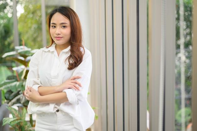 Un ritratto di donna asiatica d'affari sicura che indossa una camicia bianca in ufficio