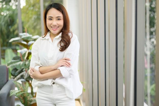 Un ritratto di donna asiatica fiduciosa di affari che indossa una camicia bianca in ufficio Foto Premium