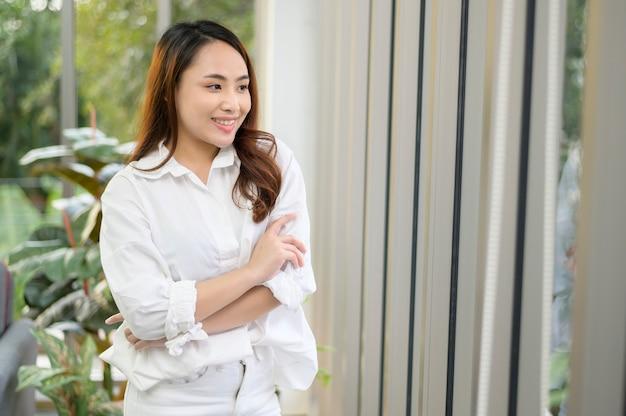 Un ritratto di donna asiatica fiduciosa di affari che indossa una camicia bianca in ufficio