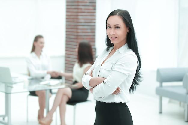 Ritratto di donna d'affari fiduciosa su sfondo ufficio sfocato.