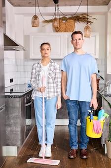 Ritratto di bidelli caucasici fiduciosi uomo e donna in piedi a casa prima della pulizia delle pulizie