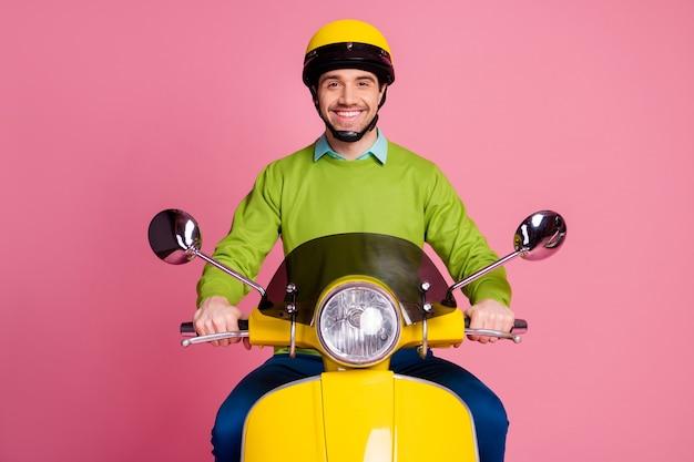 Ritratto di fiducioso ragazzo allegro in sella a ciclomotore