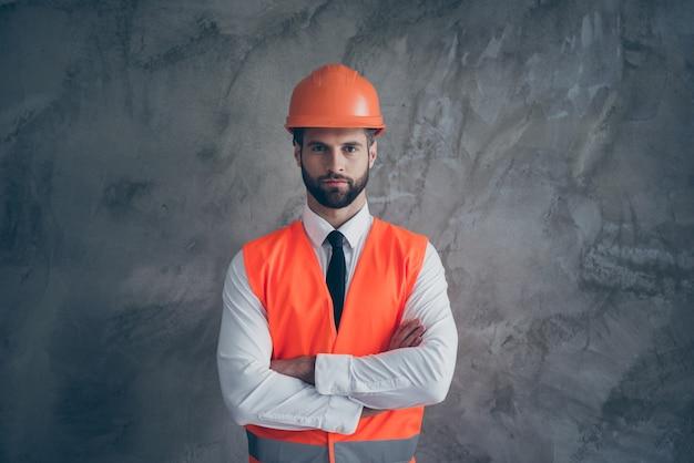 Ritratto di fiducioso costruttore cool mani incrociate pronte a costruire grande casa di costruzione indossare uniforme arancione con camicia bianca cravatta nera isolato su muro di colore grigio