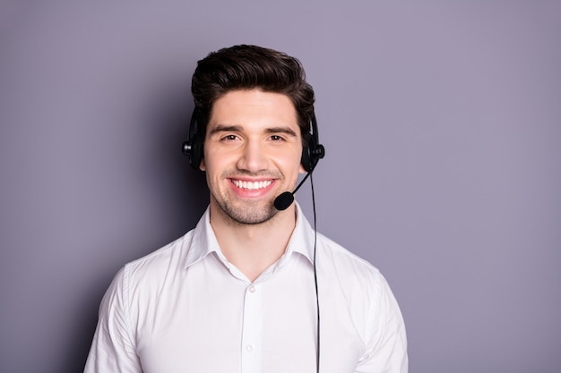 Ritratto di fiducioso lavoratore di call center positivo fresco può aiutare con problemi a indossare auricolari neri indossare abiti da cerimonia isolati su muro di colore grigio