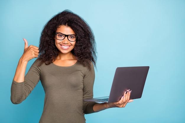 Ritratto di fiducioso cool smart mulatta ragazza tenere uso laptop mostra pollice in su come il suo lavoro sentire lei intelligente intelligente abbigliamento professionale reale elegante maglione verde isolato su parete di colore blu