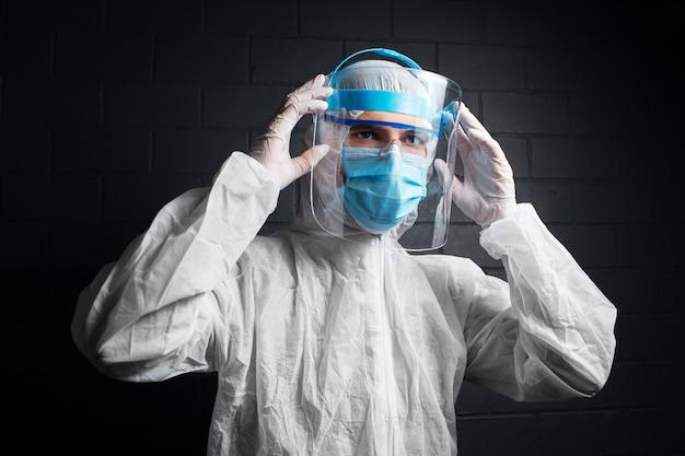 Ritratto di medico fiducioso che indossa tuta dpi contro coronavirus e covid-19.