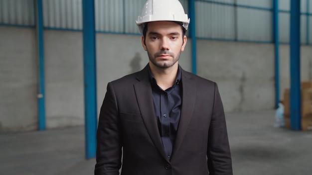 Ritratto fiducioso direttore di fabbrica che indossa tuta e casco di sicurezza in fabbrica