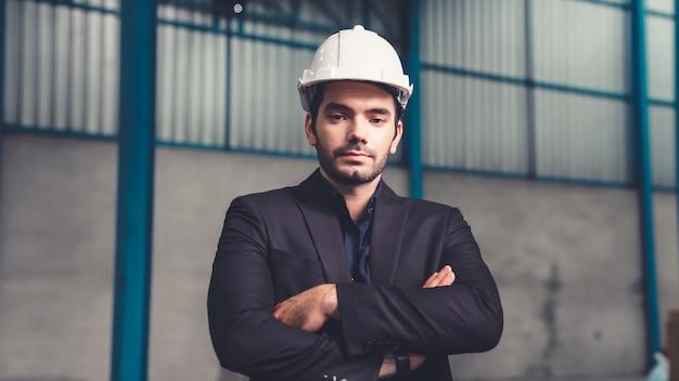Ritratto fiducioso direttore di fabbrica che indossa tuta e casco di sicurezza