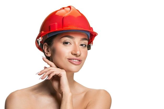 Ritratto del lavoratore sorridente felice femminile sicuro in casco arancio. donna isolata sul muro bianco. bellezza, cosmetici, cura della pelle, protezione della pelle e del viso, cosmetologia e concetto di crema
