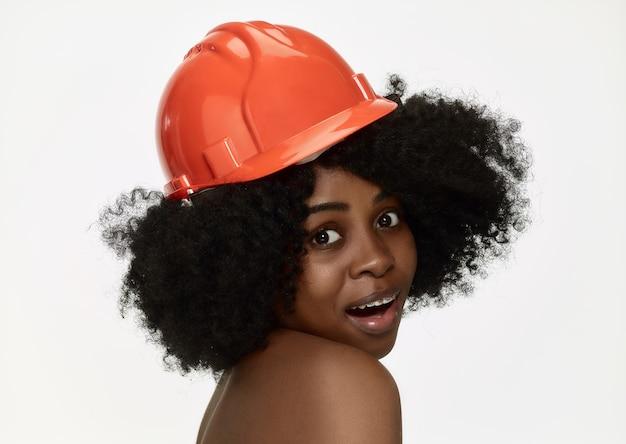 Ritratto di fiduciosa lavoratrice in casco arancione