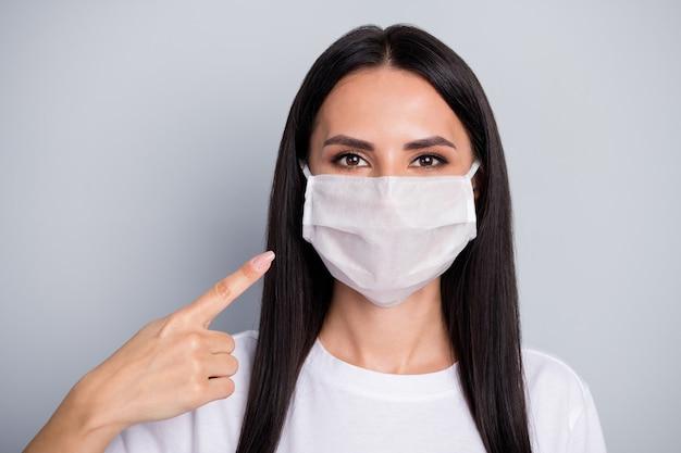 Il ritratto della maschera medica del punto del promotore della ragazza fiduciosa indica la nuova protezione di sicurezza covid29 che indossa un vestito di stile casual isolato su sfondo di colore grigio