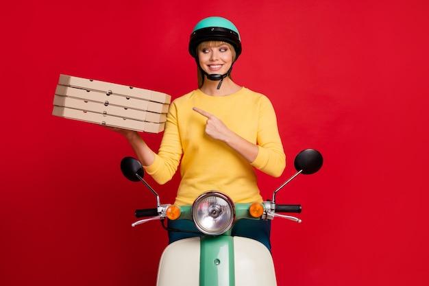 Ritratto di fiducioso ragazza seduta sul ciclomotore dimostrando pila di scatole per pizza pila