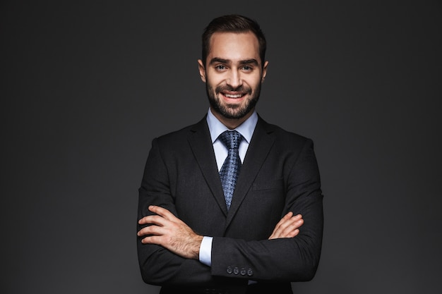 Ritratto di un uomo d'affari bello fiducioso che indossa tuta isolata, braccia conserte