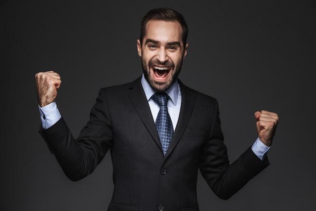 Ritratto di un uomo d'affari bello fiducioso che indossa tuta isolata, celebrando il successo
