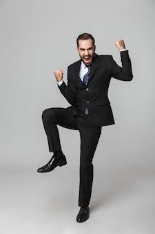 Ritratto di un uomo d'affari bello fiducioso che indossa tuta isolata, saltando, celebrando il successo