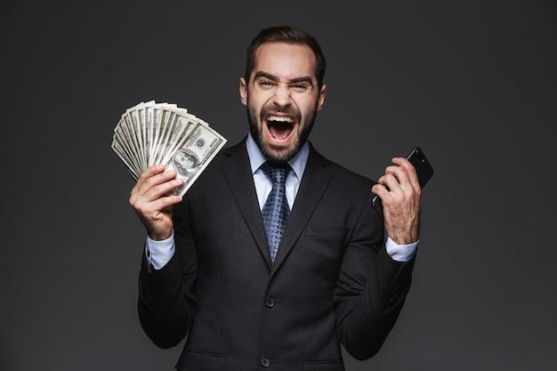 Ritratto di un uomo d'affari bello fiducioso che indossa tuta isolata, mostrando banconote di denaro, utilizzando il telefono cellulare