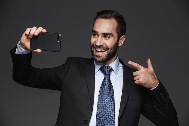 Ritratto di un uomo d'affari bello fiducioso che indossa tuta isolata, prendendo un selfie