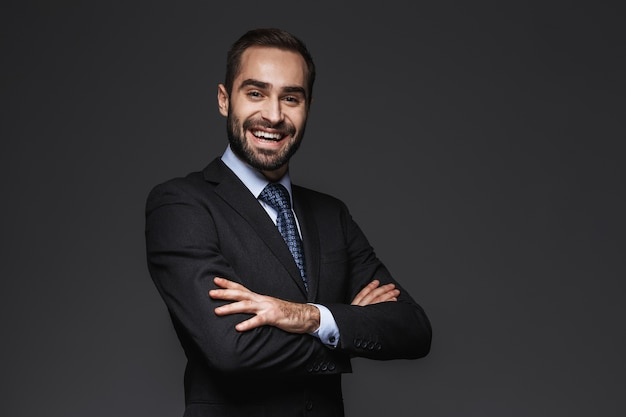 Ritratto di un uomo d'affari bello fiducioso che indossa un abito in piedi isolato, le braccia conserte
