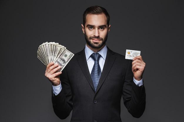 Ritratto di un uomo d'affari bello fiducioso che indossa un abito in piedi isolato, mostrando banconote di denaro, tenendo la carta di credito in plastica
