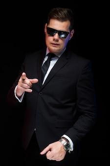 Ritratto dell'uomo d'affari bello bello sicuro in occhiali da sole che mostrano il suo potere