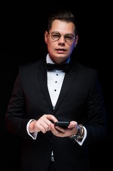 Ritratto dell'uomo d'affari alla moda elegante bello sicuro con il farfallino in vetri che tengono telefono