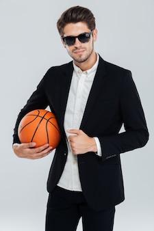 Ritratto di un bell'uomo fiducioso in occhiali da sole e abito nero che tiene palla da basket su muro grigio