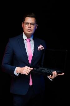 Ritratto dell'uomo d'affari serio bello sicuro che mostra computer portatile