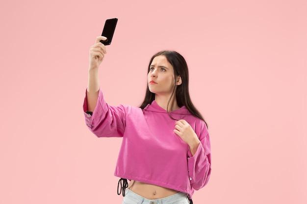 Ritratto di una ragazza casuale sorridente felice sicura che fa la foto del selfie dal telefono cellulare isolato sopra la parete rosa.