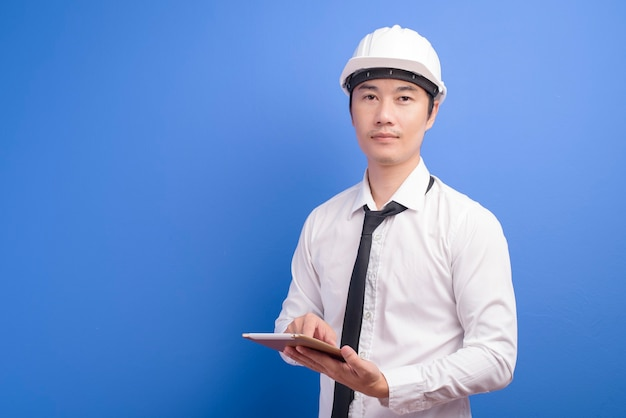 Ritratto di ingegnere maschio fiducioso che indossa un bianco utilizzando tablet su blu