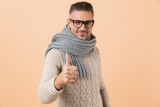 Ritratto di un uomo fiducioso vestito in maglione e sciarpa in piedi isolato sopra il muro beige, dando i pollici in su