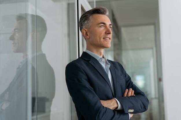 Ritratto di fiducioso imprenditore maturo con le braccia incrociate di pianificazione start up in piedi in ufficio. business di successo