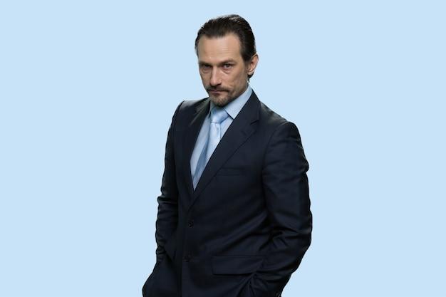 Ritratto del boss mafioso maturo sicuro. uomo d'affari di mezza età che indossa tuta protettiva e nasconde le mani nelle tasche. isolato su sfondo blu.