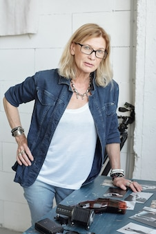 Ritratto di fiducioso fotografo maturo in giacca di jeans in piedi al tavolo e scegliendo le foto per l'album