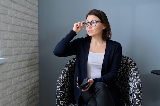 Ritratto di una donna matura sicura con gli occhiali seduto su una sedia.