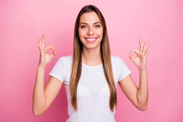 Il ritratto del promotore fiducioso positivo della ragazza fresca mostra il segno giusto consiglia le vendite del venerdì nero eccellenti indossano abiti bianchi della gioventù moderna