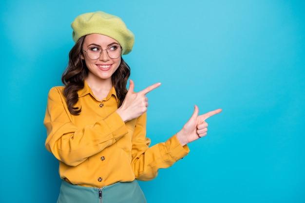 Il ritratto di una ragazza positiva fiduciosa promotrice punta il dito indice copyspace indica la promozione degli annunci di feedback indossa un copricapo di bell'aspetto isolato su uno sfondo di colore blu