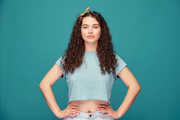 Ritratto di fiduciosa ragazza dai capelli ricci piuttosto in top raccolto tenendo le mani sui fianchi sull'azzurro