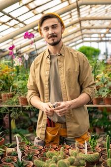 Ritratto di fiducioso giovane barbuto operaio in serra in camicia casual che tiene piccola pala in aranciera