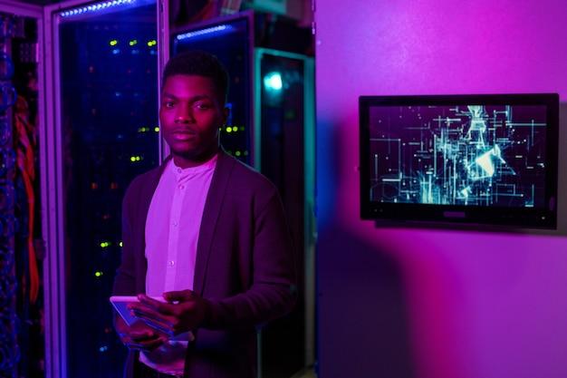 Ritratto di giovane ingegnere it nero fiducioso in cardigan in piedi con tablet in una stanza buia illuminata al neon e lavorando con un supercomputer
