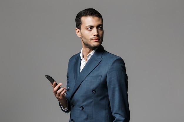 Ritratto di un giovane imprenditore fiducioso vestito in tuta in piedi isolato sopra il muro grigio, tenendo il telefono cellulare, guardando lontano