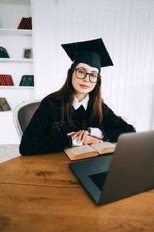 Ritratto di fiducioso giovane studentessa caucasica in libreria, celebrando la laurea.