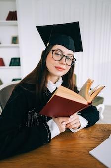 Ritratto di fiducioso giovane studentessa caucasica con libro in biblioteca, celebrando la laurea.